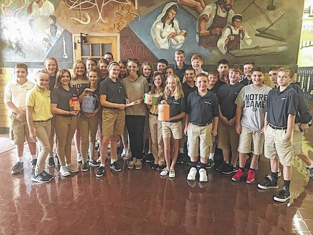 The 7th grade class presenting a check for $500 to Paul & Megan Baum. Paul & Megan work for Adore Ministries.