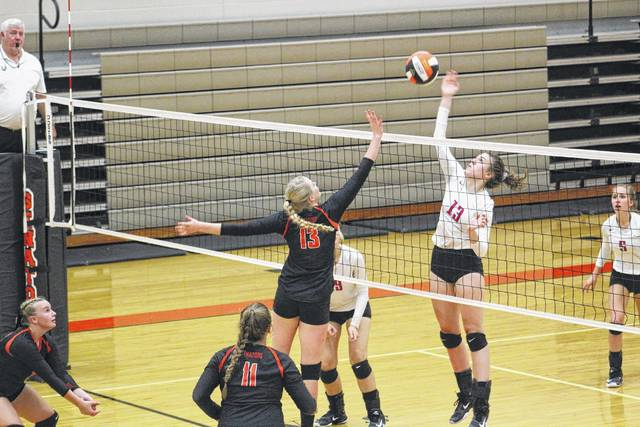 Anne Marie Raies of Portsmouth and Morgan Rigsby from West battle at the net for a ball.