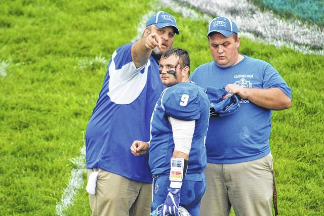 East head coach James Gifford talks with quarterback Brady Douthat before the game.