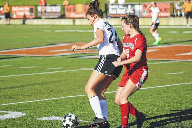 Wheelersburg's McKailyn Wamsley (24) and Minford's Aurie Coriell (3) fight for control of the ball.