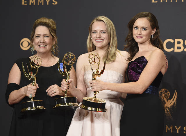 """FILE - In this Sept. 17, 2017 file photo, Ann Dowd, from left, winner of outstanding supporting actress in a drama series, Elisabeth Moss, winner of outstanding lead actress in a drama series, and Alexis Bledel, winner of outstanding guest actress in a drama for """"The Handmaid's Tale"""" pose in the press room at the 69th Primetime Emmy Awards at the Microsoft Theater in Los Angeles. The Nielsen company, which has long measured viewership of television programs, announced Wednesday, Oct. 18, says it has a way to collect and widely spread details about how many people watch programming produced by streaming services.  (Photo by Jordan Strauss/Invision/AP, File)"""