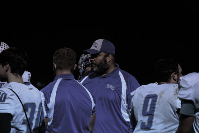 East head coach James Gifford meets with his players during a timeout.