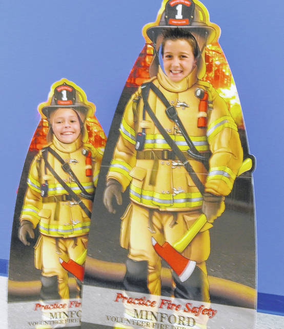 Taylor Cron and Brody McGuire, third graders at Minford Elementary posing in the firemen cutouts.