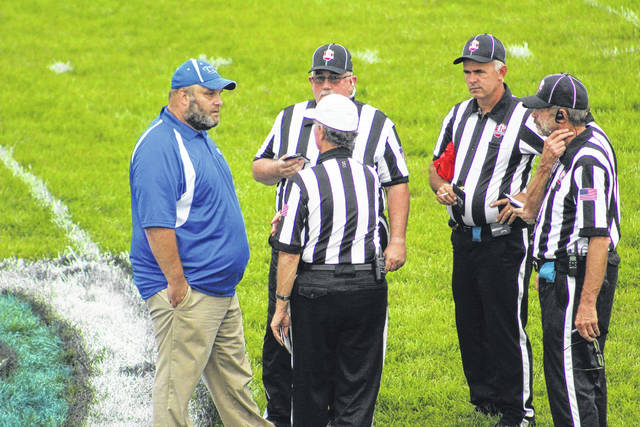 East HC James Gifford talks to officials before the game against Green earlier this season.
