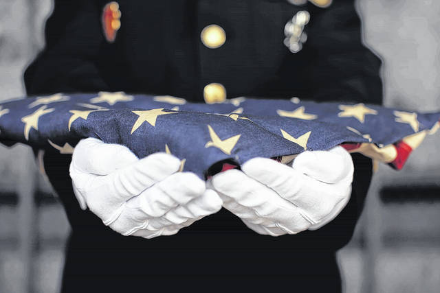 Military personnel holding a folded US flag.