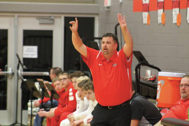 Head coach Adam Cox signals in a play from the sidelines.