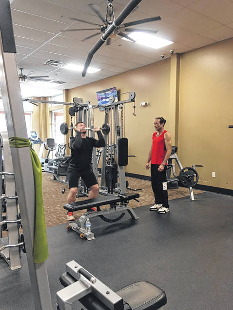 Aaron Ostrowski, trainer, at AnyTime Fitness demonstrating lifting with a member