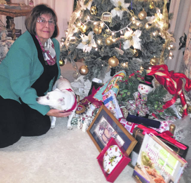 Prizewinner Sandra Reiser sitting next to her dog and Christmas tree.