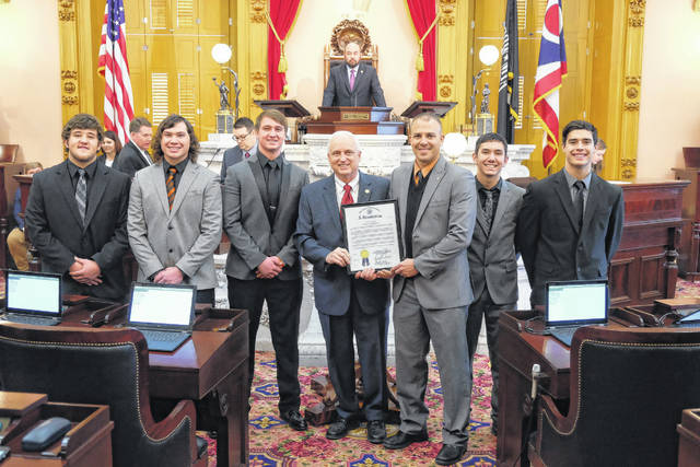 From left to right: CJ Hall, Nic Parsley, Xander Carmichael, State Rep. Terry Johnson (R), Wheelersburg head coach Rob Woodward, Bryson Keeney, and Alex George stand with the resolution honoring the Wheelersburg football program for its 2017 Division V State Championship.