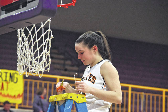 Wheelersburg's Abbie Kallner cuts a piece of the net down as Wheelersburg celebrates its sectional title.