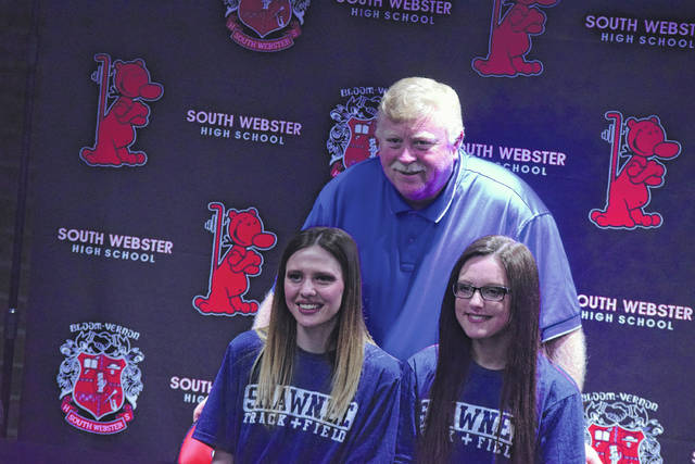 South Webster's Hailey Marshall (left) and Kayleigh Blevins (right) pose for a picture with South Webster cross country coach Tim Conley (center).