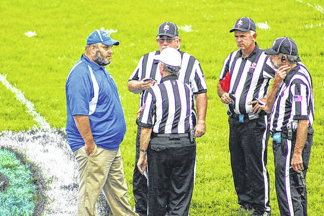 East's James Gifford talks with referees before the Tartans' contest against Green back in the fall. Gifford officially made the move to South Point after accepting the head coaching spot on Monday evening.