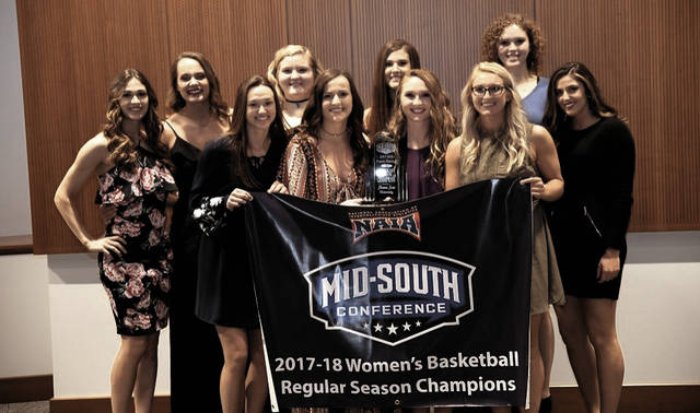 The 2017-18 Shawnee State Bears stand with their regular season championship banner.