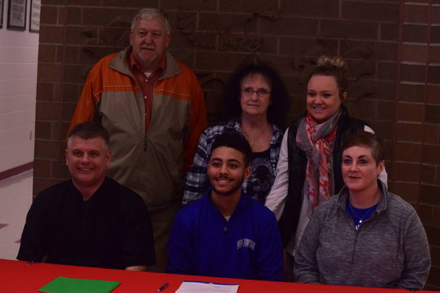 Elijah Craft with Shawn Kelley (front row, left), Stephanie Craft (front row, right), and family members at Minford High School during his signing ceremony.