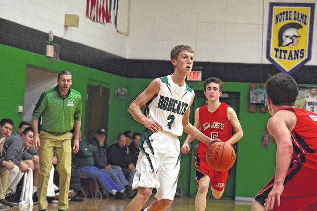 Green's Tanner Kimbler moves up the floor with the basketball against South Webster in early February.