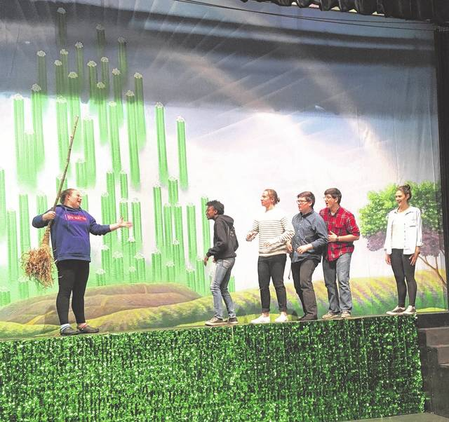 "Portsmouth High School students — portraying (from left) the Wicked Witch of the West, Dorothy, Tin Man, Scarecrow, Lion and Glinda the Good Witch of the South — rehearse a scene from ""The Wizard of Oz."""