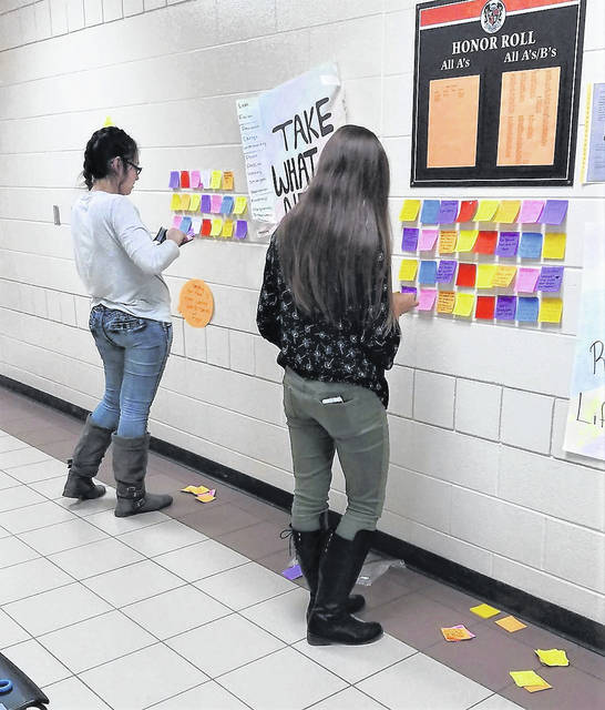 """Students place inspirational notes on the """"Wall of Positivity."""""""