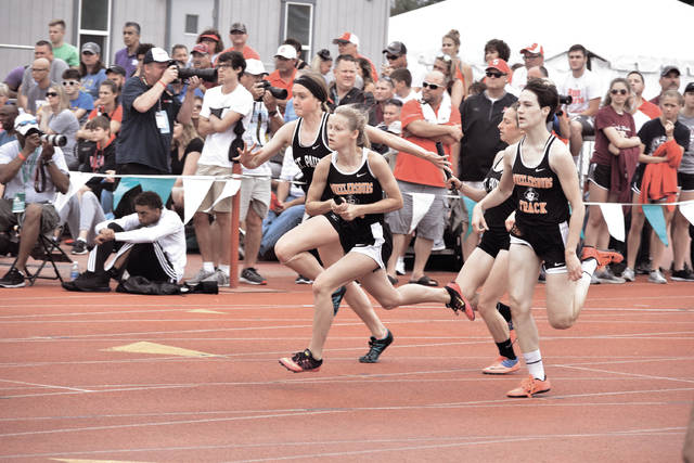 Wheelersburg's Gabby Deacon hands the baton off to fellow teammate Lani Irwin.