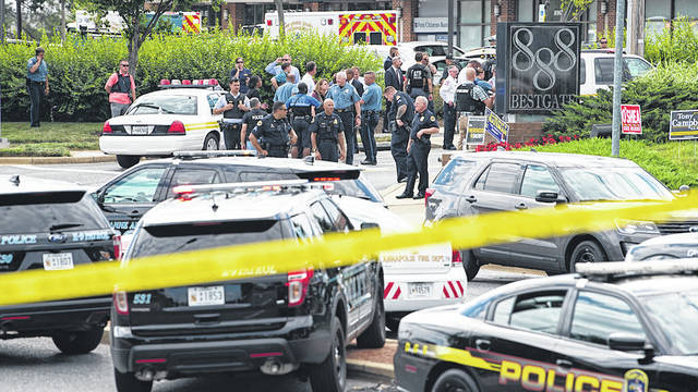 Police secure the scene of a shooting at the building housing The Capital Gazette newspaper in Annapolis, Md.