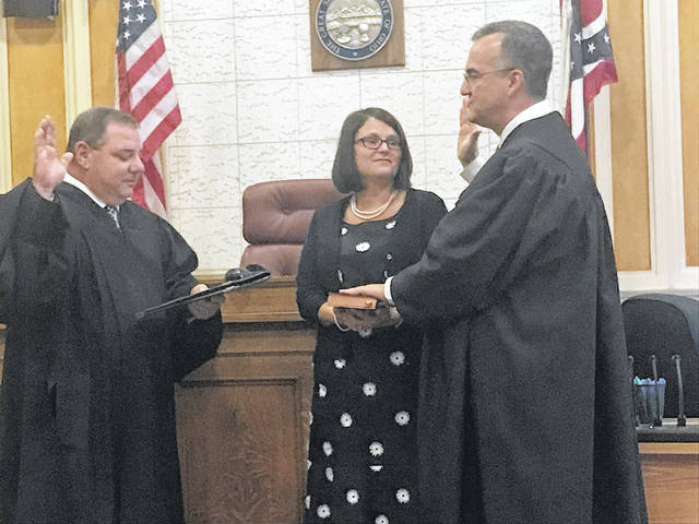 Now former Scioto County Prosecutor Mark Kuhn became county Common Pleas Judge Mark Kuhn after being sworn into office Thursday afternoon. Fourth District Court of Appeals Judge Matthew McFarland did the honors in the very courtroom in which Kuhn will be presiding beginning Monday. Looking on was the new magistrate's wife Kari Kuhn. Kuhn was nominated for the bench by Gov. John Kasich. County commissioners have four to 45 days after Mark Kuhn formally takes office to name a new interim prosecutor.