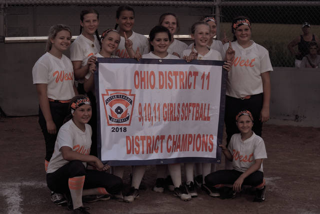 The West 11U Softball All-Stars with their district title banner.