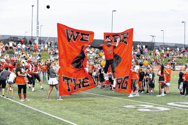 Wheelersburg wide recevier Tanner Holden leads the Pirates onto the field to begin the 2018 season.